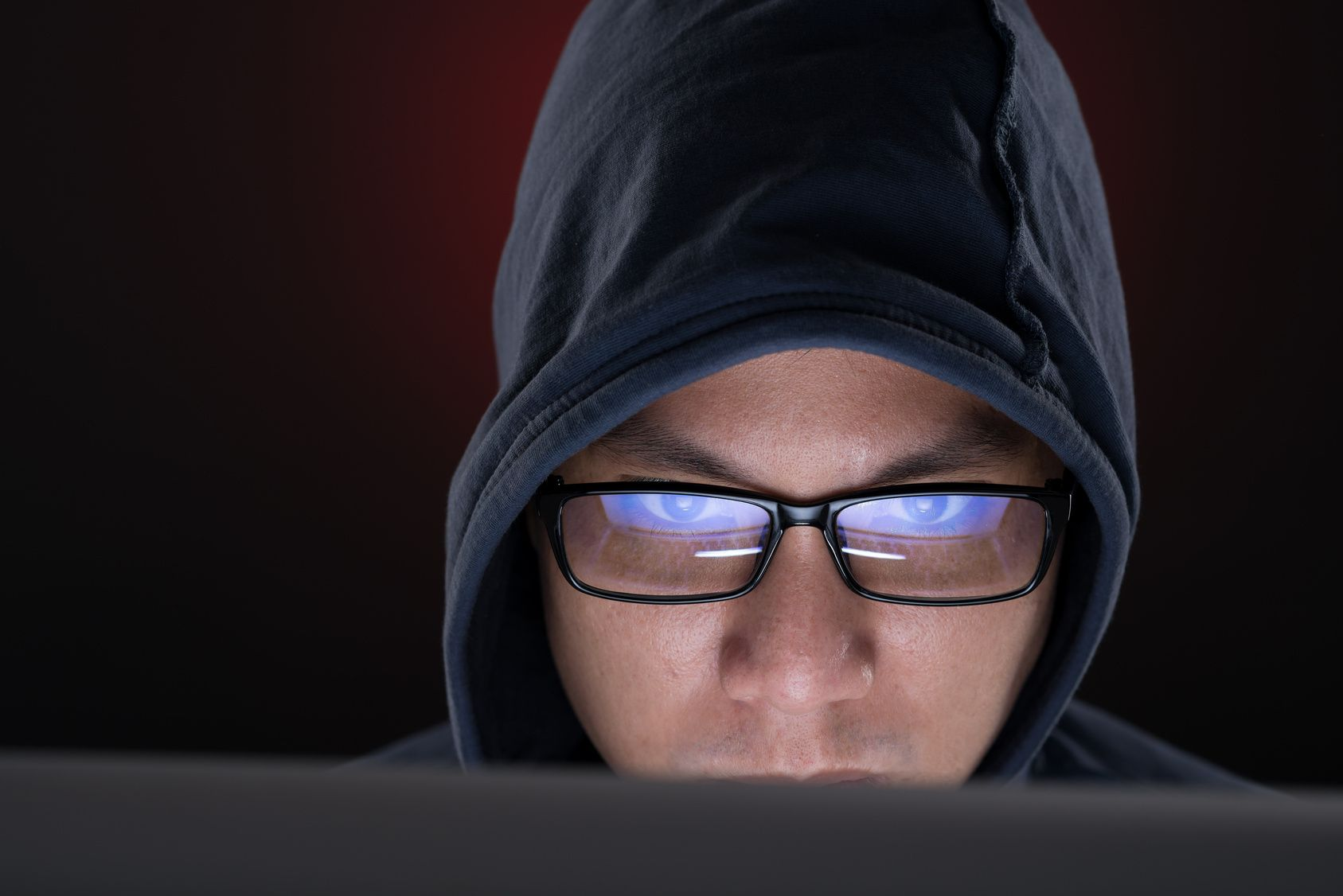 Close-up of hooded man hacking computer